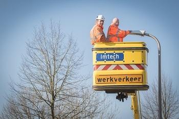 Wethouder Jan Steenbergen helpt met het aanbrengen van LED verlichting langs de Schutlandenweg.